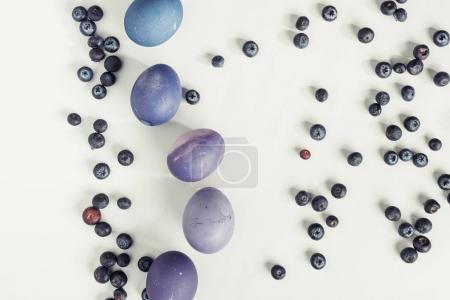top view of blueberries and painted violet easter eggs on grey