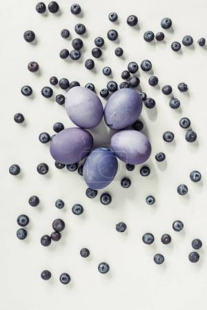 top view of purple painted easter eggs and blueberries on grey
