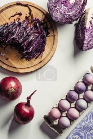 top view of purple cabbage, onions and painted eggs in egg box on grey