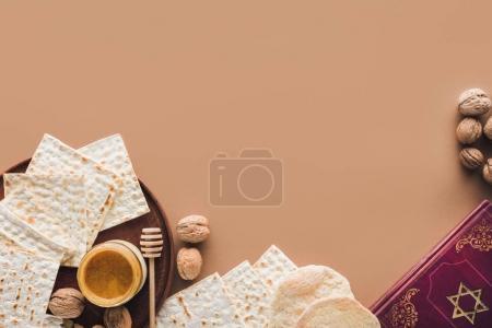 Photo pour Vue du haut du livre traditionnel avec texte en hébreu et matza avec miel sur la surface brune - image libre de droit