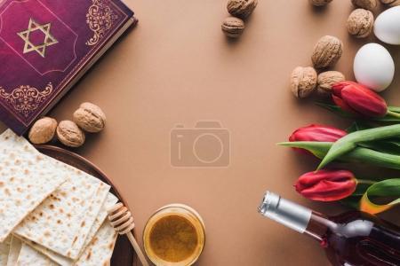 Photo pour Vue du haut du livre traditionnel avec texte en hébreu, vin et matza sur table - image libre de droit