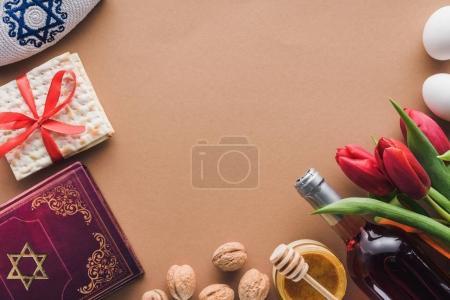 Photo pour Vue du haut du livre traditionnel avec texte en hébreu, vin et matza sur table brune - image libre de droit