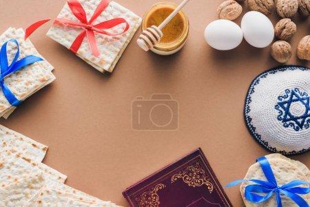 Photo pour Vue du haut du livre traditionnel avec texte en hébreu, kippah et matza sur table brune - image libre de droit