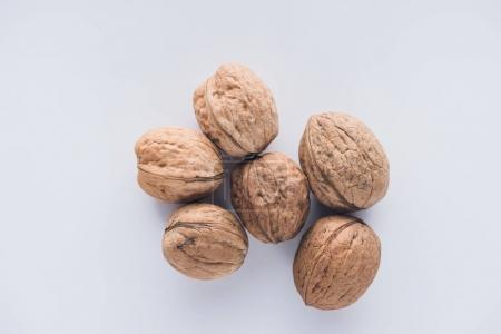 Top view of six walnuts on white surface