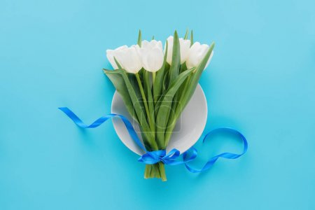 Top view of white tulips on plate isolated on blue