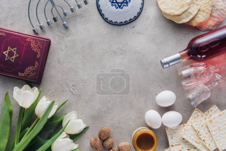 top view of traditional book with text in hebrew, menorah and kippah on concrete table