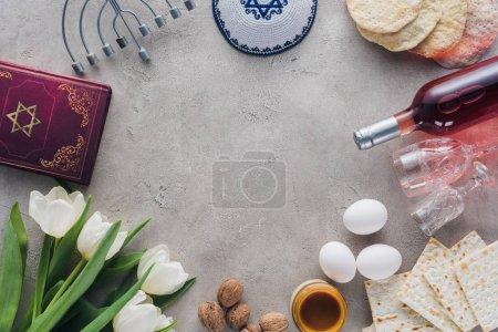 Photo pour Vue du haut du livre traditionnel avec texte en hébreu, menorah et kippah sur table en béton - image libre de droit