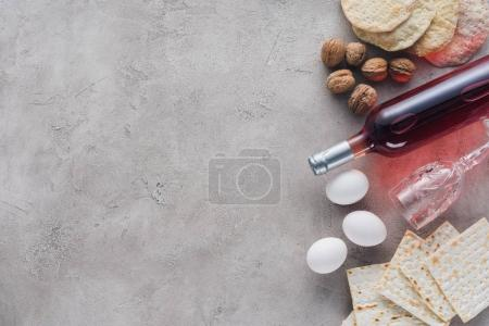 top view of wine, matza and chicken eggs on concrete surface, Pesah celebration concept
