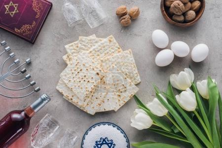 top view of traditional book with text in hebrew, matza and menorah on concrete table