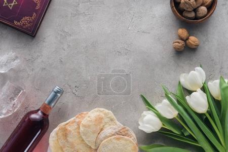 top view of traditional book with text in hebrew, matza and wine on concrete table