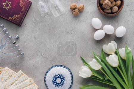 top view of traditional book with text in hebrew, kippah and menorah on concrete table