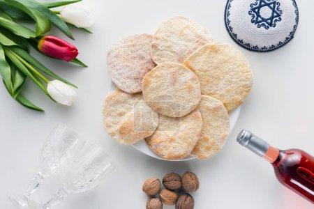 Photo pour Vue du dessus du matza et du vin sur table blanche, concept de célébration Pesah - image libre de droit