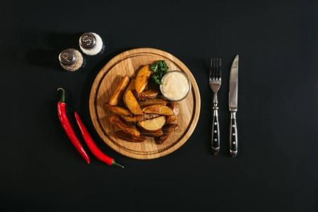 delicious baked potatoes with sauce on wooden board, spices, chili peppers and fork with knife on black
