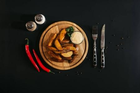 tasty roasted potatoes with sauce on wooden board, spices, chili peppers and fork with knife on black