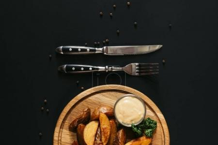 top view of tasty roasted potatoes with sauce on wooden board and fork with knife on black