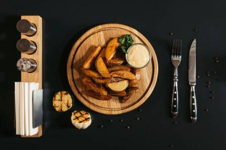 top view of delicious roasted potatoes with sauce on wooden board, grilled garlic and fork with knife on black