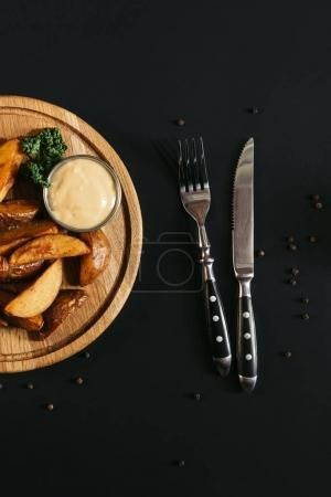 top view of baked potatoes with sauce on wooden board and fork with knife on black