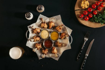 top view of delicious roasted chicken with various sauces on baking paper, spices, glass of beer and vegetables on black