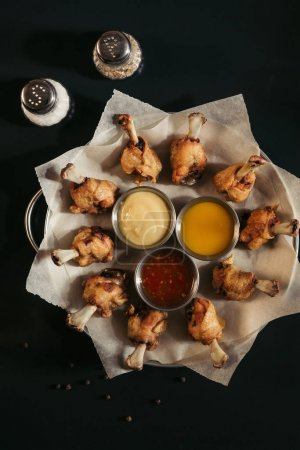 top view of delicious roasted chicken with various sauces on baking paper and spices in black