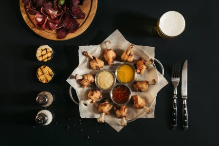 top view of delicious roasted chicken with various sauces on baking paper and glass of beer on black