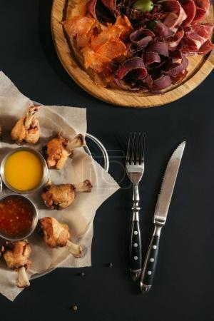 delicious roasted chicken with various sauces, gourmet assorted meat and fork with knife on black
