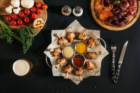 top view of delicious roasted chicken with various sauces, assorted meat and vegetables on black