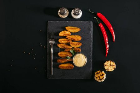 top view of tasty baked potatoes with sauce and fork on slate board and spices with garlic and chili peppers on black