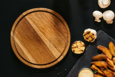 top view of empty wooden board, grilled garlic, mushrooms and baked potatoes with sauce on black