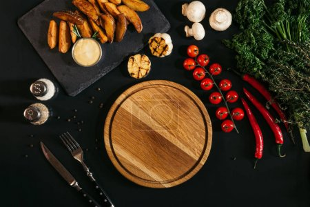 top view of empty wooden board, vegetables and baked potatoes on black