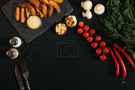 Photo pour Vue de dessus des pommes de terre cuites au four savoureuses avec sauce, épices et légumes sur noir - image libre de droit