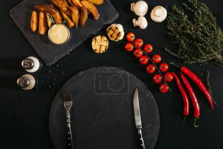 top view of empty slate board with fork and knife, baked potatoes, spices and vegetables on black