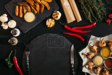 top view of empty slate board with fork and knife, roasted potatoes and vegetables on black