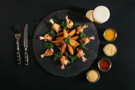tasty roasted potatoes with chicken, various sauces, fork with knife and glass of beer on black