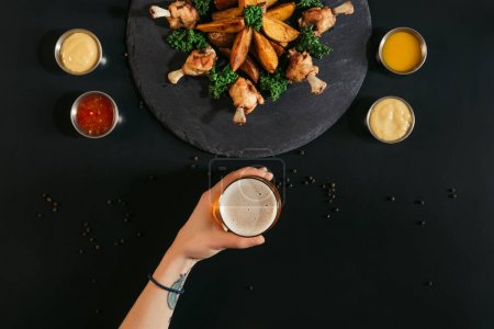 cropped shot of person holding glass of beer while eating delicious roasted potatoes with chicken and sauces on black