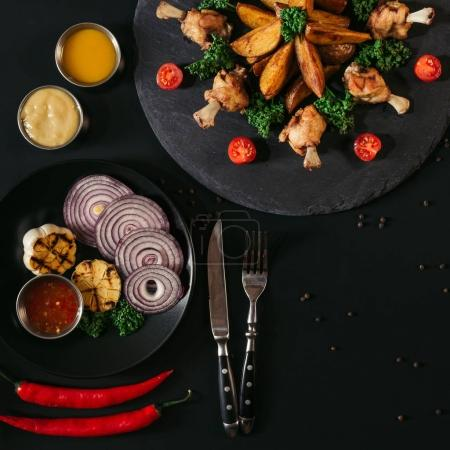 top view of delicious baked potatoes with fried chicken wings, sauces and vegetables on black
