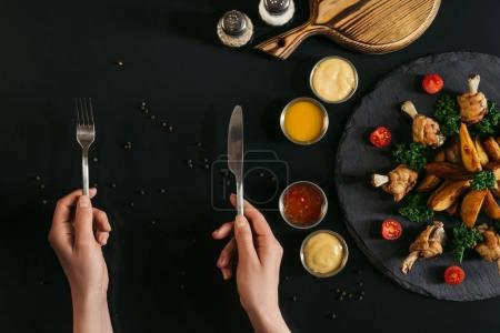 partial top view of person holding fork and knife and tasty baked potatoes with roasted chicken and sauces on black