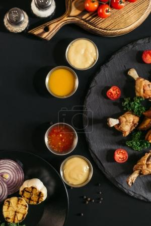 top view of tasty roasted chicken wings with various sauces and vegetables on black