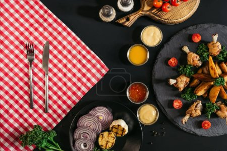 top view of checkered napkin with fork and knife, vegetables, sauces and delicious roasted potatoes with chicken on black