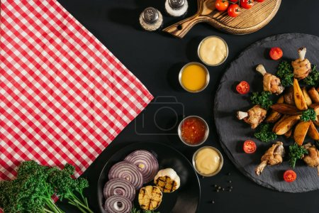 top view of checkered napkin, vegetables, sauces and delicious roasted potatoes with chicken on black