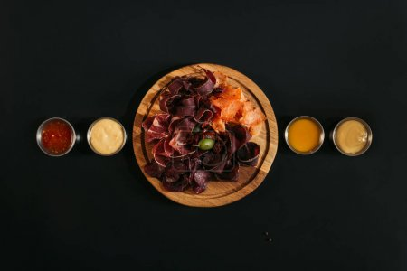 top view of delicious sliced assorted meat on wooden board with various sauces on black
