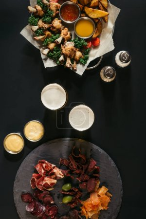 top view of glasses of beer, assorted meat and fried potatoes with chicken on black