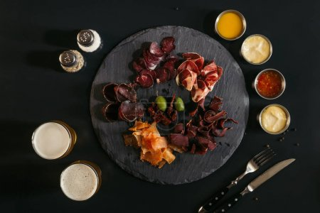 top view of gourmet assorted meat on slate board, various sauces and glasses of beer on black