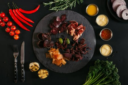 top view of gourmet assorted meat on slate board, various sauces and vegetables on black