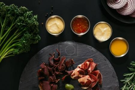 top view of gourmet craft meat with various sauces on black