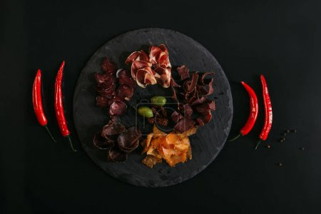 top view of gourmet assorted meat with olives on slate board and chili peppers on black