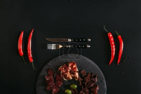 top view of gourmet assorted meat on slate board, fork with knife and chili peppers on black