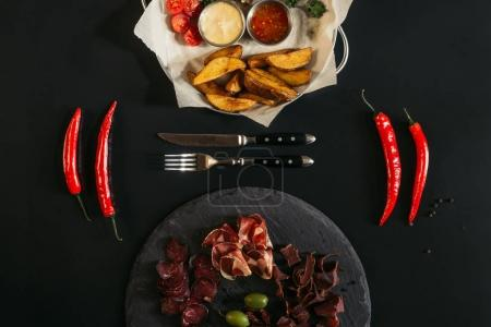 top view of baked potatoes with sauces, chili peppers, fork, knife and gourmet assorted meat on slate board on black