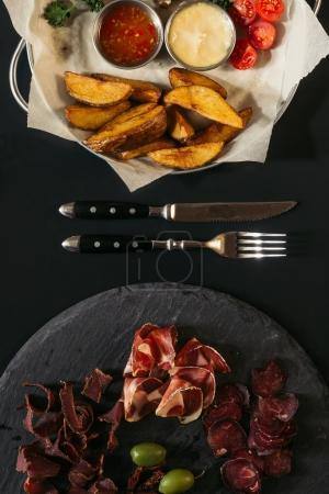top view of delicious assorted meat on slate board and roasted potatoes on baking paper with fork and knife on black