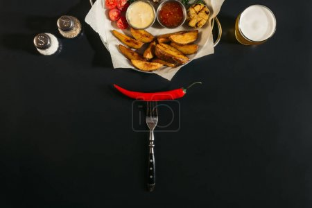 top view of red hot chili pepper on fork and delicious roasted potatoes with sauces on black