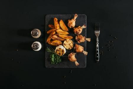 top view of delicious roasted potatoes with chicken and grilled garlic on slate board on black